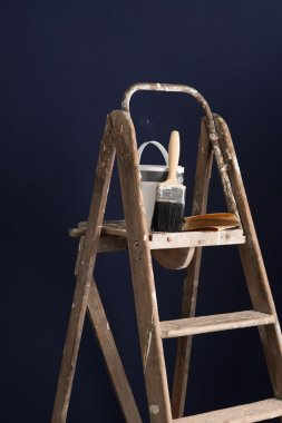 Old Stepladder with Paint Bucket and Brush Over Dark Backdrop