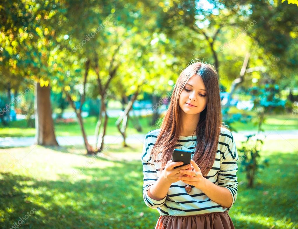 Happy beautiful young Caucasian girl with smart phone outdoors on sunny summer day tex-ting and smiling