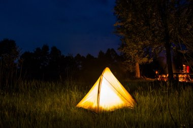 Yellow tent lighting at night in wildness