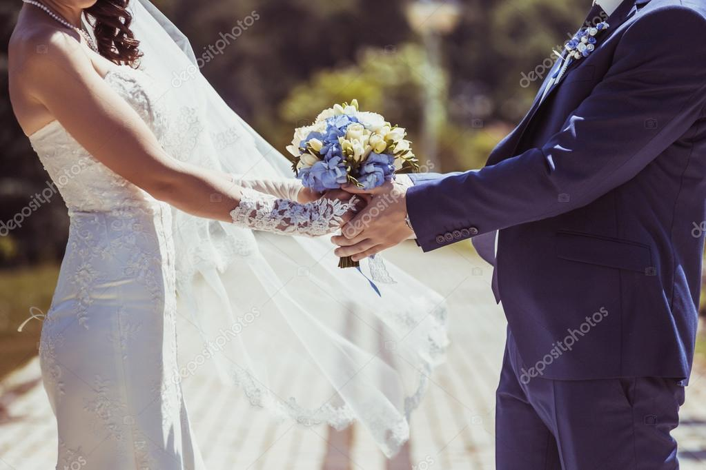 Wedding couple holding hands in sunny wedding day