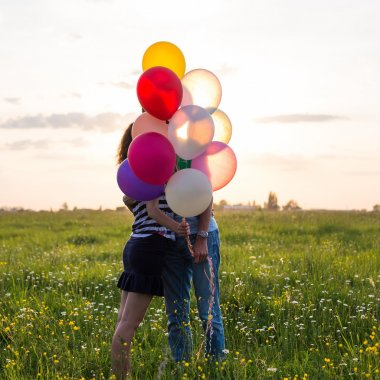 Couple in love are kissing and holding multicolored balloons in beautiful sunset