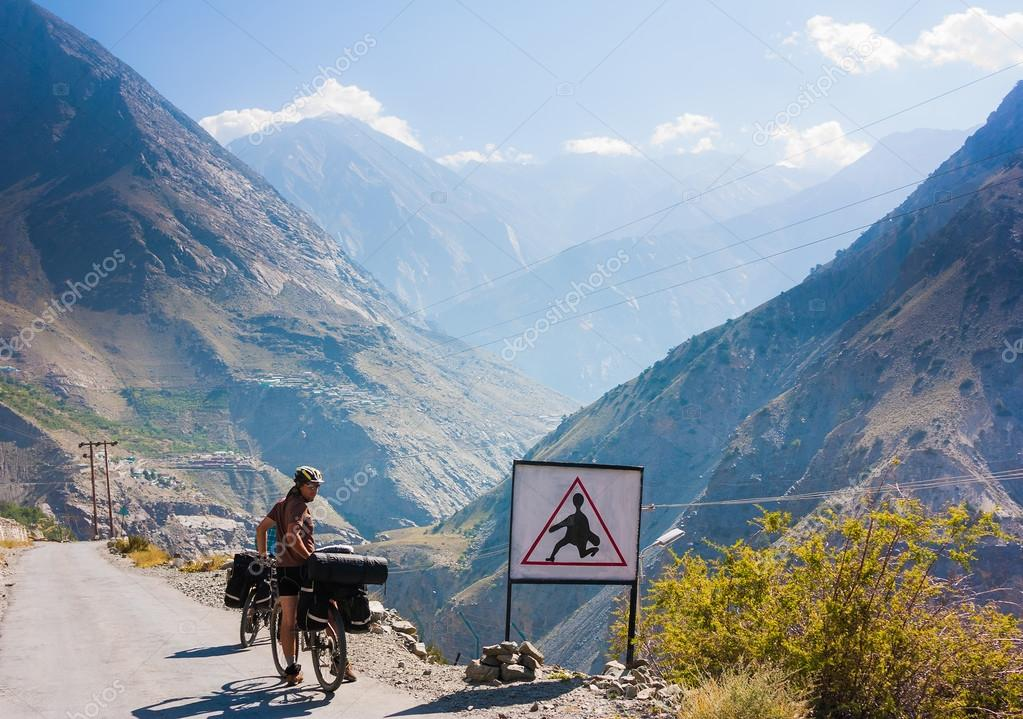 Bicyclist riding in fantastic landscape on mountain road, Jammu and Kashmir State, North India