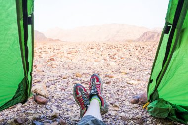 Legs with red sneakers in green tent