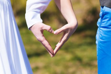 Bride and groom make heart with hands