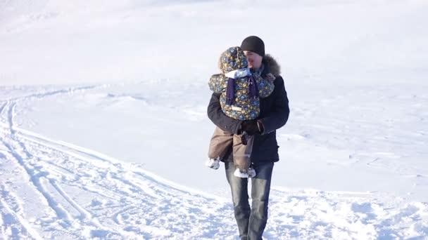 Šťastný muž se dvěma malými dětmi, zábava na sněhu