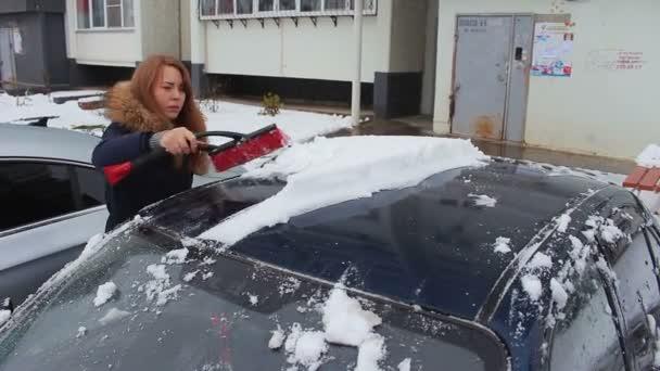 Jedna dívka čistí auto od sněhu