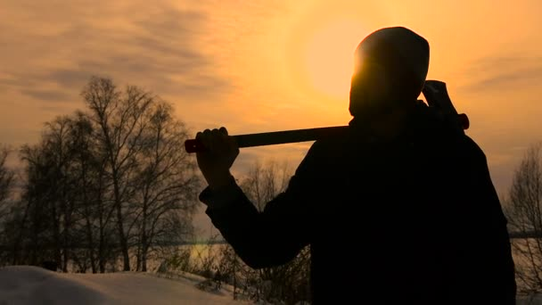 Silhouette Lumberjack standing with his ax in sunset time