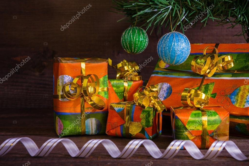 Viele Weihnachtsgeschenke unter dem Baum mit Dekorationen und ribb ...