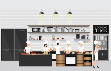 Chefs cooking at the table in restaurant kitchen interior.