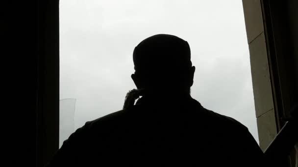 terrorista con pistole guardando fuori dalla finestra, rallentatore