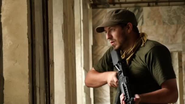Terrorista con pistole guardando fuori dalla finestra