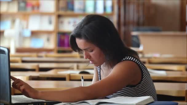 gyönyörű lány diák a könyvtárban