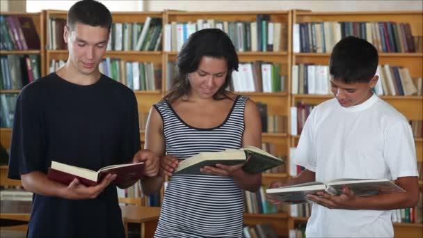 studenti v knihovně při pohledu na fotoaparát a usmívá se