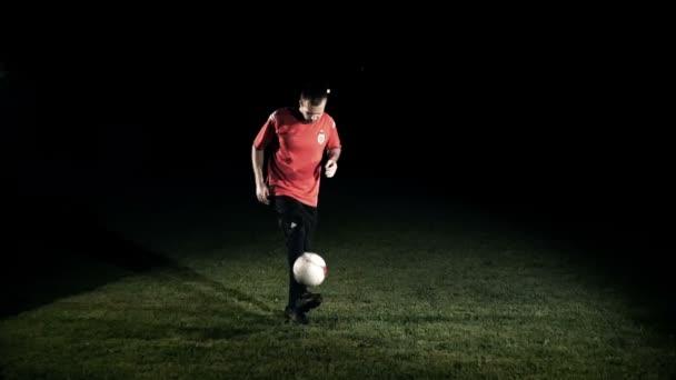 Zsonglőrködik a labdát lassított férfi futballista