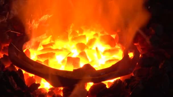 Kovář se ohřívá podkovy v ohni