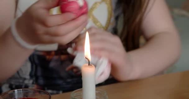 Mädchen-Farben auf Osterei mit Kerze