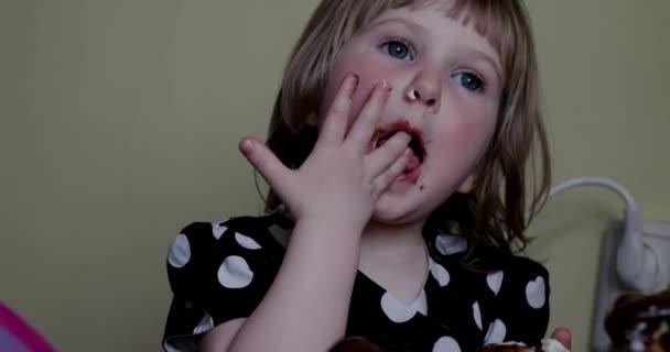 Malá holčička lízání čokolády z prstu, jíst čokoládové košíčky