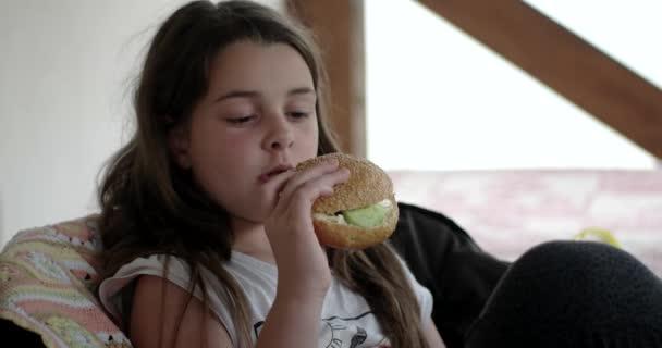 Šťastná dívka jí velký chutný Hamburger na verandě