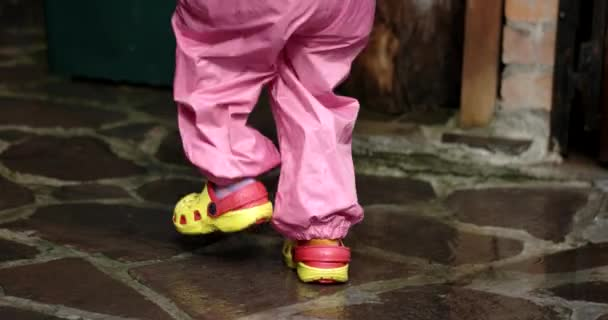 Feet of a Kid Jumping in Sandals Through Puddles