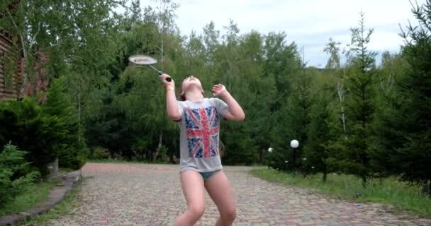 Holčička s raketou a kuželka hrát Badminton a bavit venku
