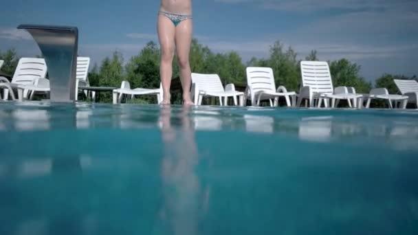 Happy aktivní dívka skákání a potápění v plavání bazén - pomalý pohyb podvodní záběr