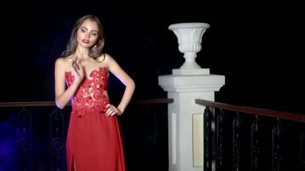 A piros ruhás lány áll az erkélyen