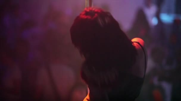 Girl dancing striptease on pylon in the night club