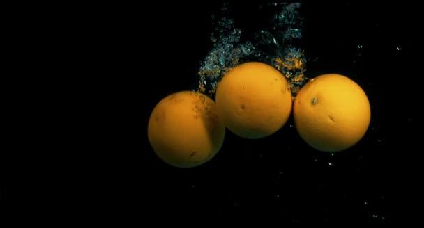 Pomeranče, spadající do vody v pomalém pohybu na černém pozadí
