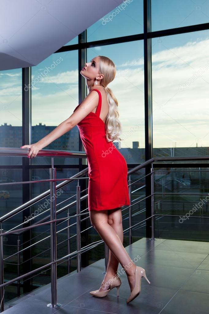 5e507a549108f7 Mooie glamoureuze blonde meisje in een rode jurk poseren in de buurt van  glazen vitrine — Foto van davstudio