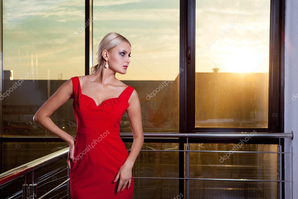 263d64808c8f04 Mooie glamoureuze blond meisje in een rode jurk poseren in de buurt van de  showcase van