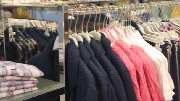 Panorama pohled oblečení na ramínkách v obchodě
