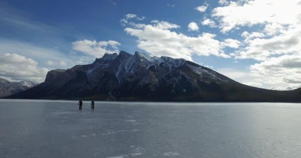 Pan záběr na cyklisty a turisty na zamrzlém jezeře se skalnatými horami v pozadí
