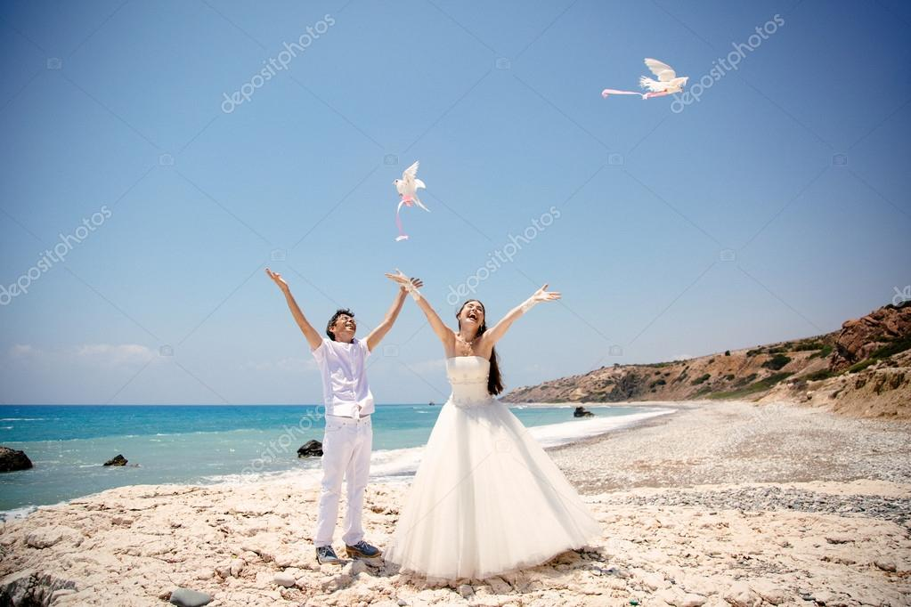 Happy smiling bride and groom hands releasing white doves on a sunny day.  Mediterranean Sea. Cyprus