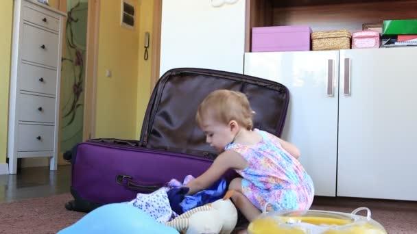 malá holčička rozbalí vaku po cestování