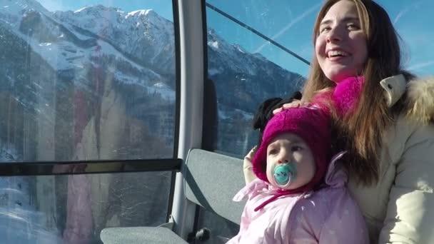 mladá matka se svou malou dcerou jízdu na lanové dráhy v horách za slunného dne v zimě. Zpomalený pohyb
