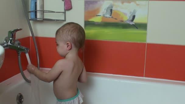 Vicces baba kislány a fürdőben játszó vízcseppek és mosás arcát
