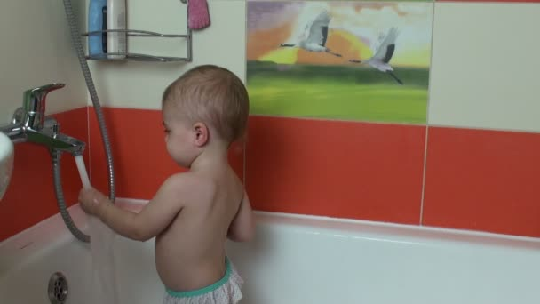 Funny little baby girl in the bath playing with water drops and washing his face