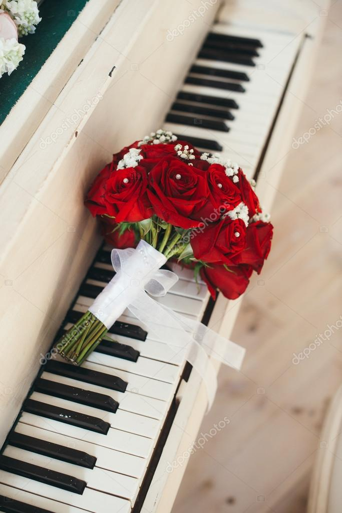 The bridal bouquet from roses lies on piano keys