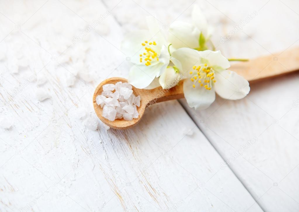 Spa composition with jasmine flowers and sea salt on white wooden table