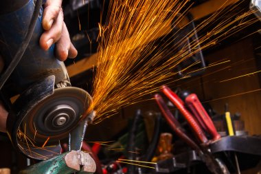 Worker cutting metal with grinder. Sparks while grinding iron. S