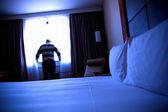 férfi egy szállodai szobában az ablak mellett