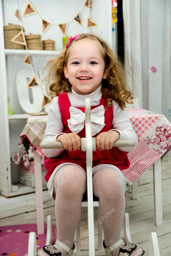 Little lovely smiling girl on the wooden toy horse in the interi