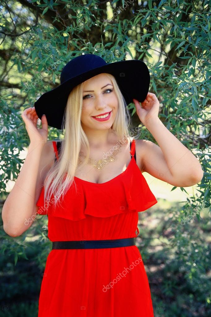 girl in red dress and black hat smile — Stock Photo © Ribalka  112978628 f4fa306aa12
