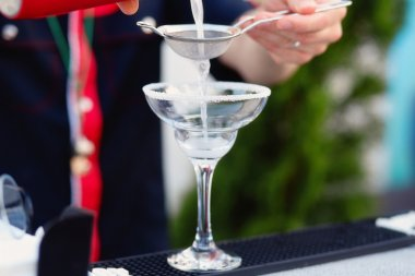 Bartender preparing cocktail for guests