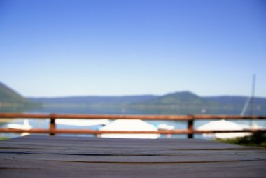 Wood table top on blur lake background