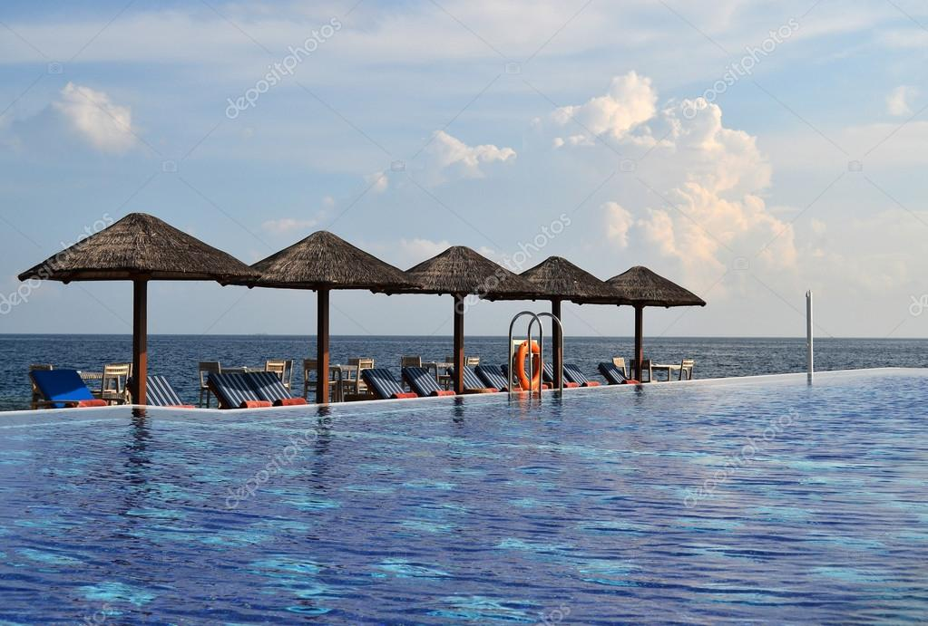 Piscina con hamacas y sombrillas naturales foto de stock for Hamacas de piscina