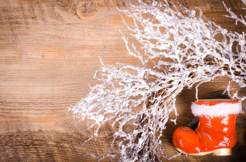 Christmas snowy wreath and Santa Claus boots on wooden background, New Year decoration. Free space for text.