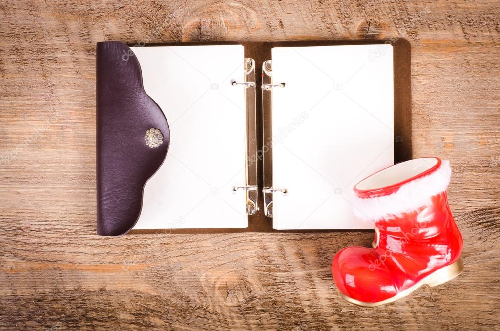 Santa Claus boots and blank wish book on wooden background, New Year and Christmas decoration, card. Free space for text.