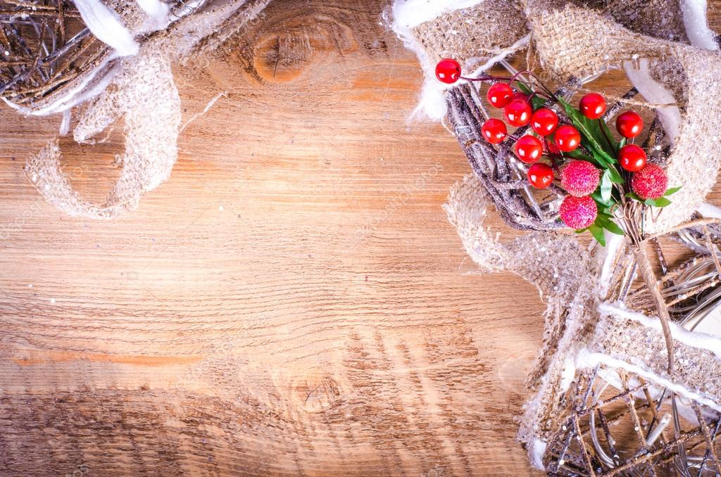 Christmas rustic light boxes on wooden background, sprig of berries, snowy wreath. Christmas and New Year decoration frame. Free space for text.