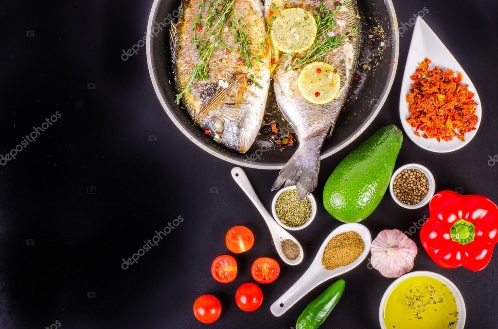 Gebratene Dorade Fische mit Zitrone, Kräutern, Salz auf schwarzem ...